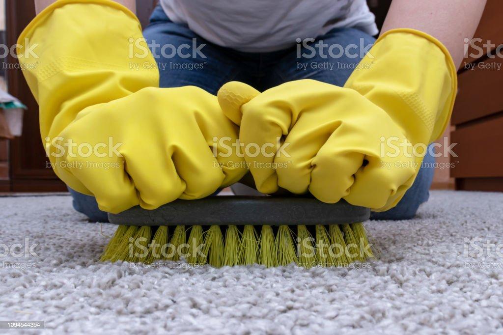https www istockphoto com fr photo nettoyage de tapis avec une brosse les mains dans des gants de caoutchouc jaune fait gm1094544354 293770483