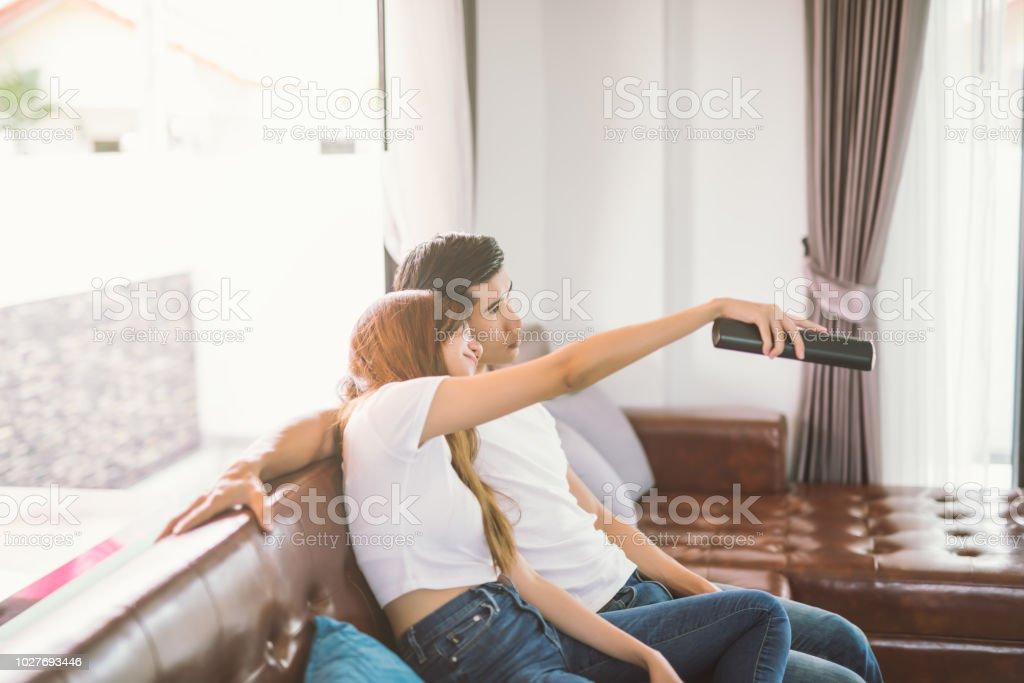 https www istockphoto com fr photo couple sur le canap c3 a9 avec tv distance regarder la t c3 a9l c3 a9vision dans le salon gm1027693446 275523730
