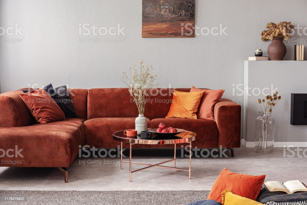 https www istockphoto com photo fashionable velvet corner sofa with pillows next to elegant coffee table with flowers gm1176275522 327883925