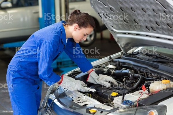 A Female Mechanic Working Under The Hood Of A Car Stock ...