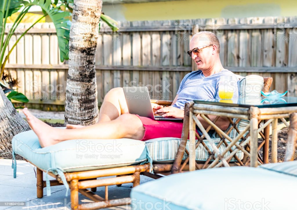 https www istockphoto com photo guy in his forties uses laptop outdoors on porch or patio in backyard gm1218041049 355781360