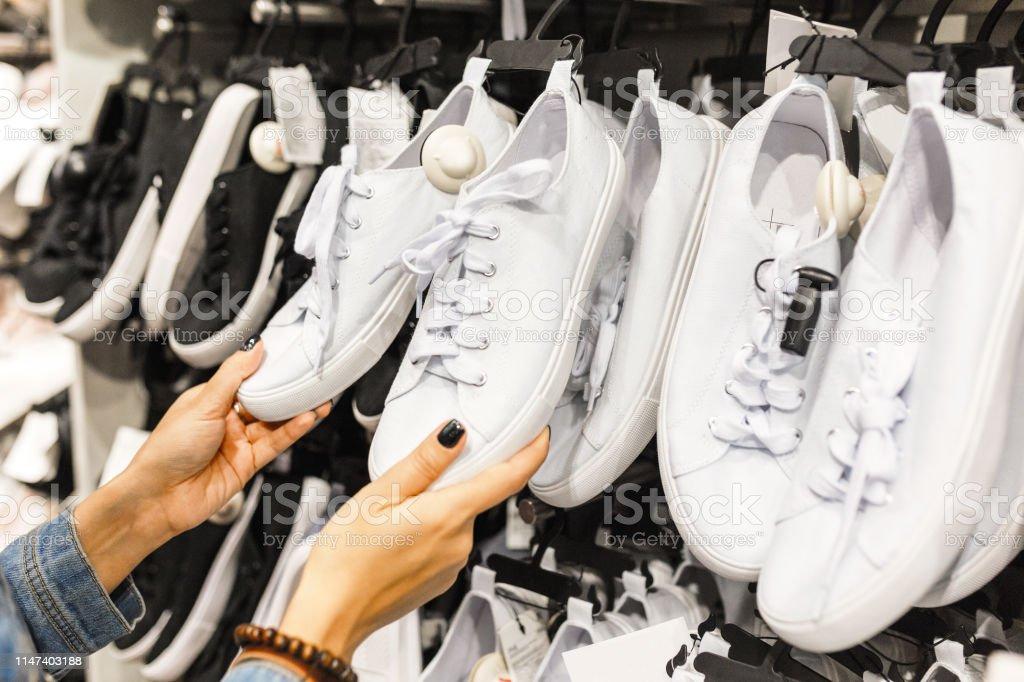 Photo Libre De Droit De Client Heureux De Jeune Femme Choisissant La Paire De Chaussures De Baskets Et Lachetant Dans Le Magasin De Vetements Concept De Magasinage Occasionnel Banque D Images Et Plus