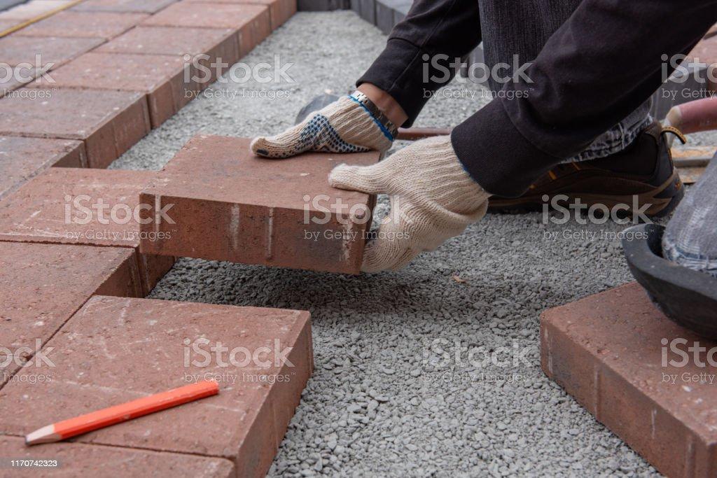 instalacion de ladrillos de pavimentadora para patio en patio trasero las manos enguantadas de un obrero usan un martillo para colocar adoquines de piedra foto de stock y mas banco de imagenes