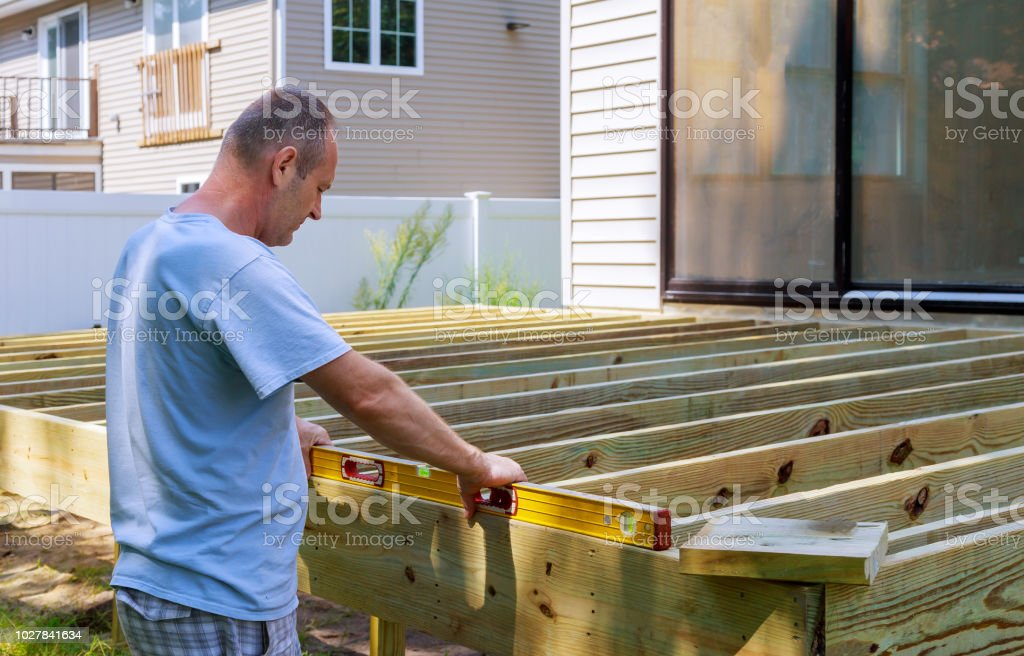 man building a wooden patio with hammering screwing together beams stock photo download image now istock