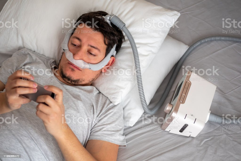 man wearing under the nose nasal mask and using cpap machine for sleeping smoothly and playing with his smart phone before sleeping stock photo download image now istock