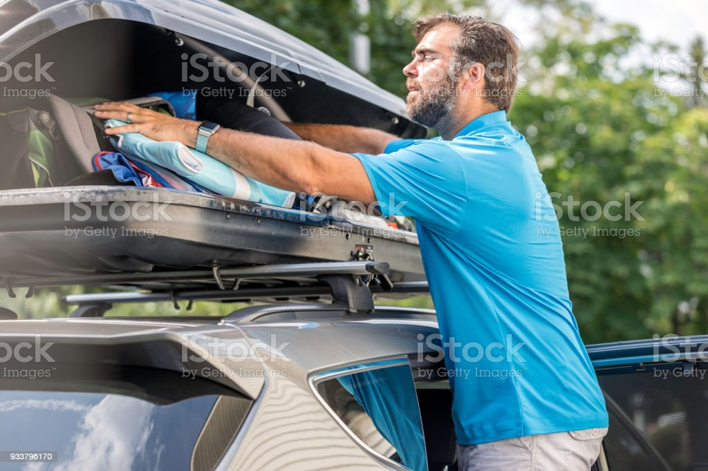 men filling cargo box container on roof rack for vacations or camping stock photo download image now istock