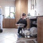 A Nineyearold Boy Helping To Unpack The Dishwasher At Home Stock Photo Download Image Now Istock
