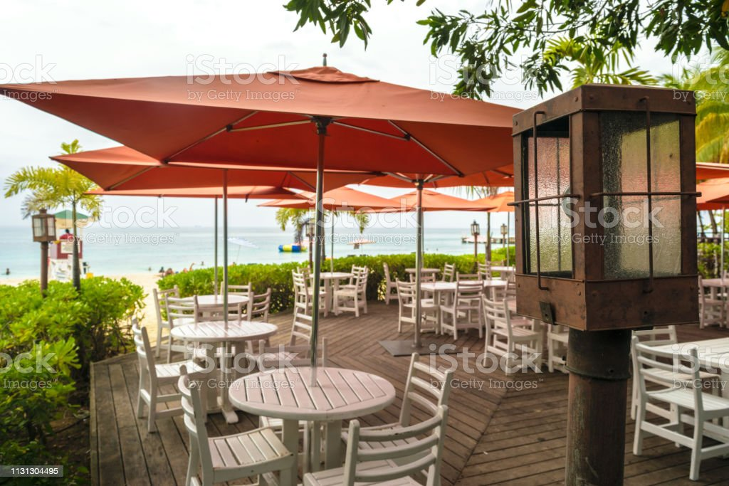 outdoor beach restaurant with wooden floors and large patio umbrellas stock photo download image now istock