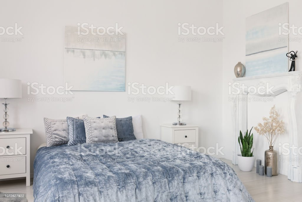 Pillows On Blue Bed Between Lamps On Cabinets In White Bedroom Interior With Posters Real Photo Stock Photo Download Image Now Istock