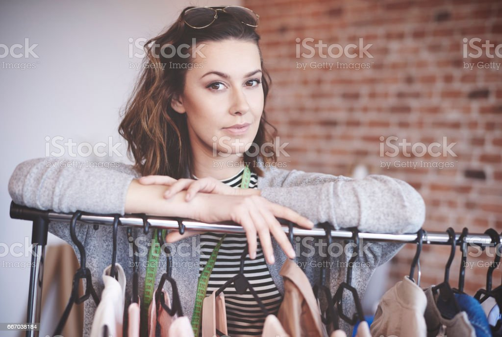 https www istockphoto com photo portrait of young tailor leaning the clothes rack gm667038184 121665857