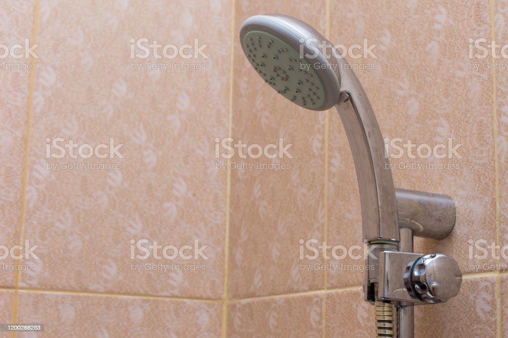 https www istockphoto com photo rain shower head in the bathroom handing on orange tile for cleaning and bathing gm1200288263 343746145