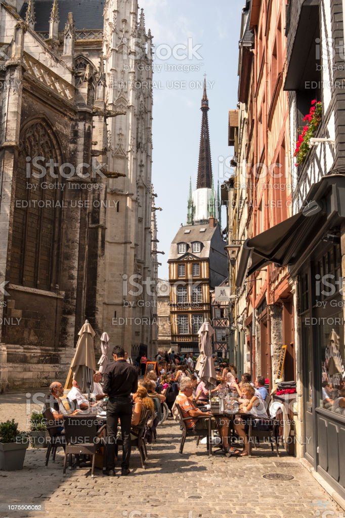 https www istockphoto com photo residents of the city and tourists relax in a cafe near the church of saint maclou gm1075506062 287942602