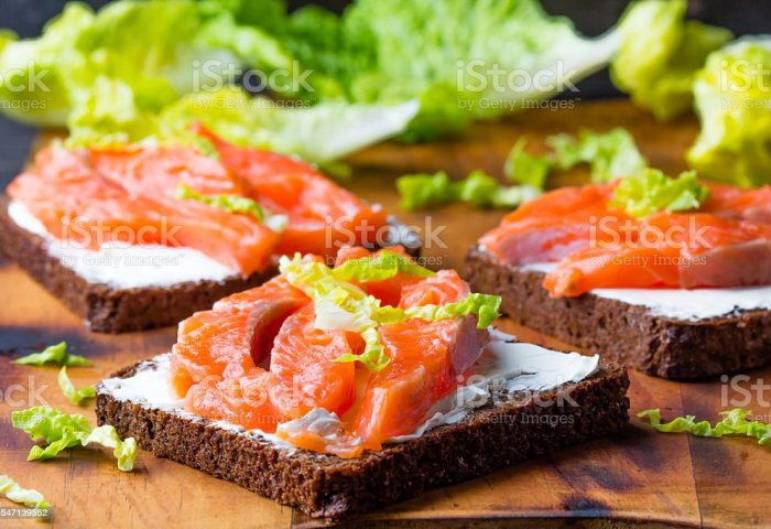 Sandwich With Cereals Black Bread And Salmon On Wooden Board Stock