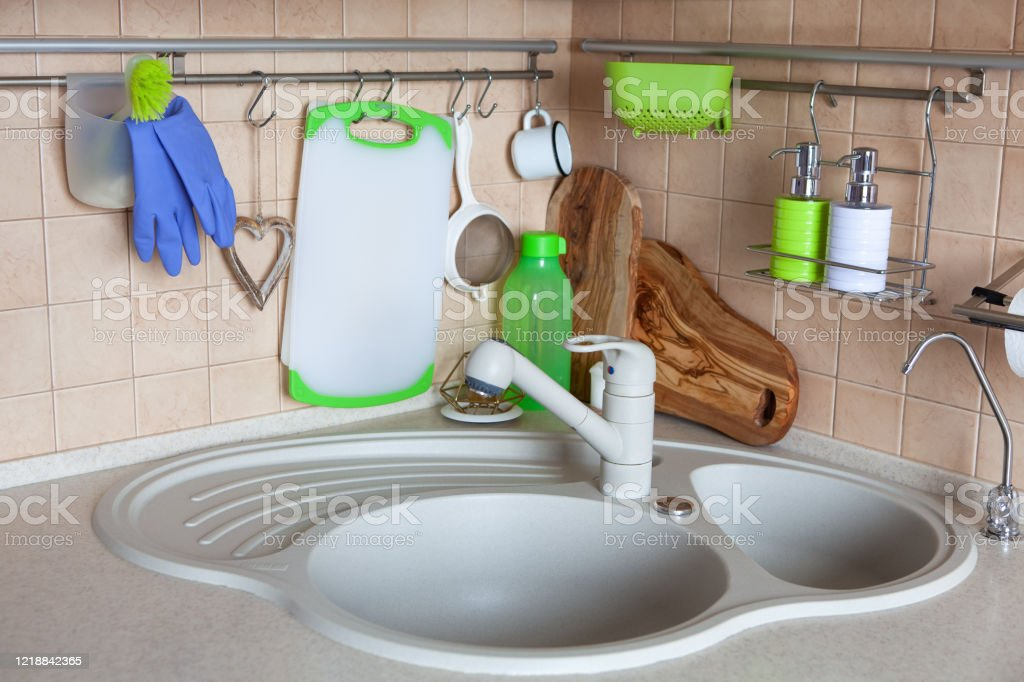 side view of the modern kitchen in bright colors a round corner sink accessories for washing dishes and cleaning interior details in daylight concept real modern interior household horizontal stock photo