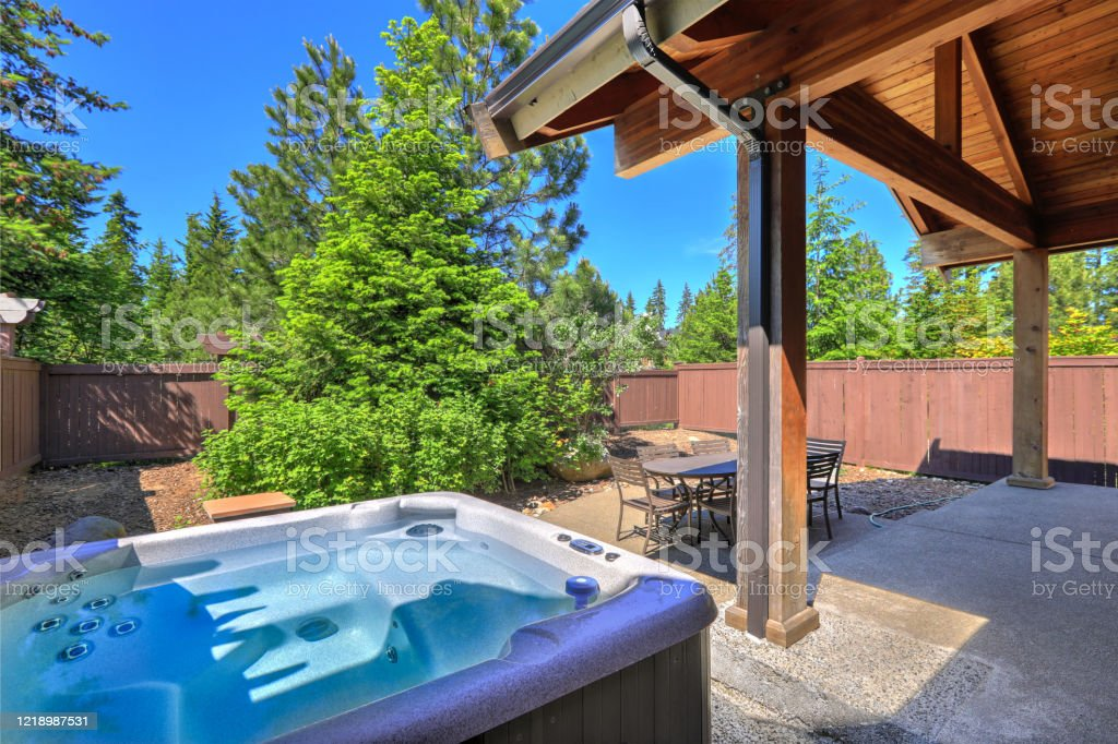 small fenced back yard space with dining room table and hot tub surrounded by trees stock photo download image now istock
