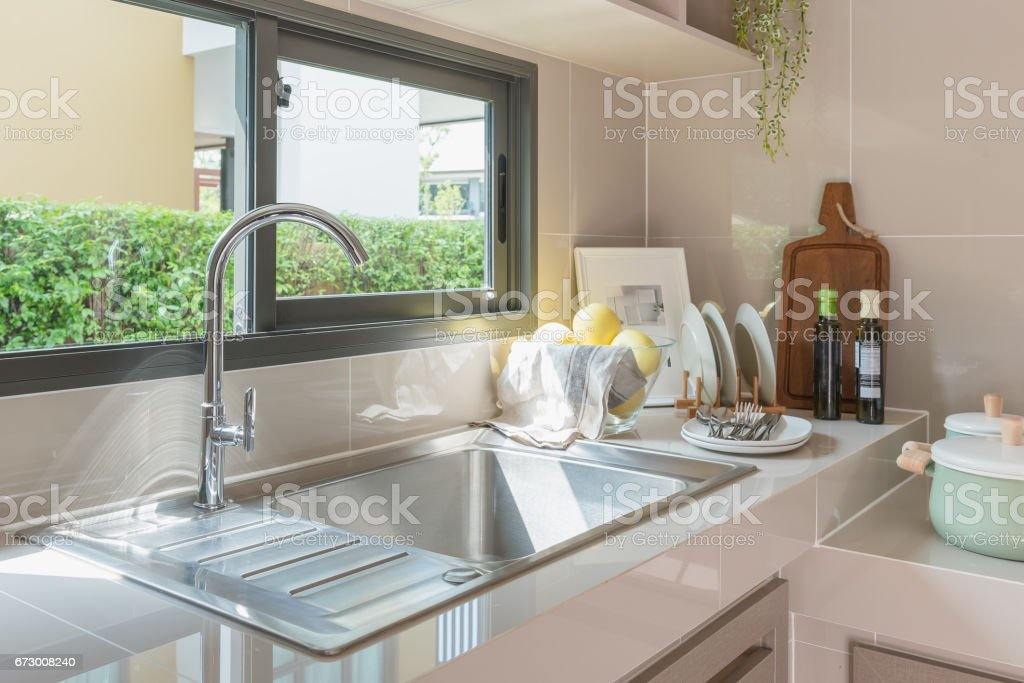 https www istockphoto com photo stainless steel sink with faucet on kitchen counter gm673008240 123277789