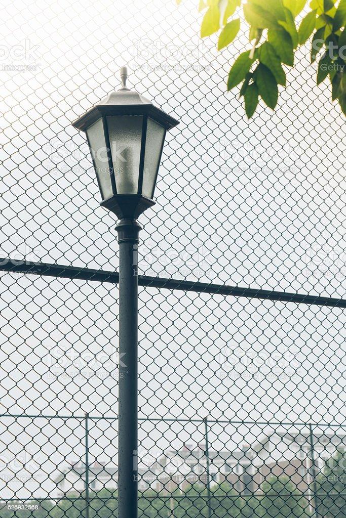 https www istockphoto com photo street lamp post standing front of steel fence gm626932568 110914381