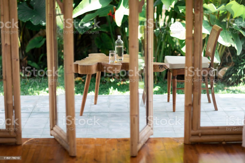 https www istockphoto com photo table from tree stump with glass bottle of water standing it home terrace gm1163176010 319309226