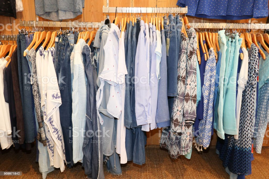 various color shirts cloth hang on a shelf in a designer clothes store stock photo download image now istock