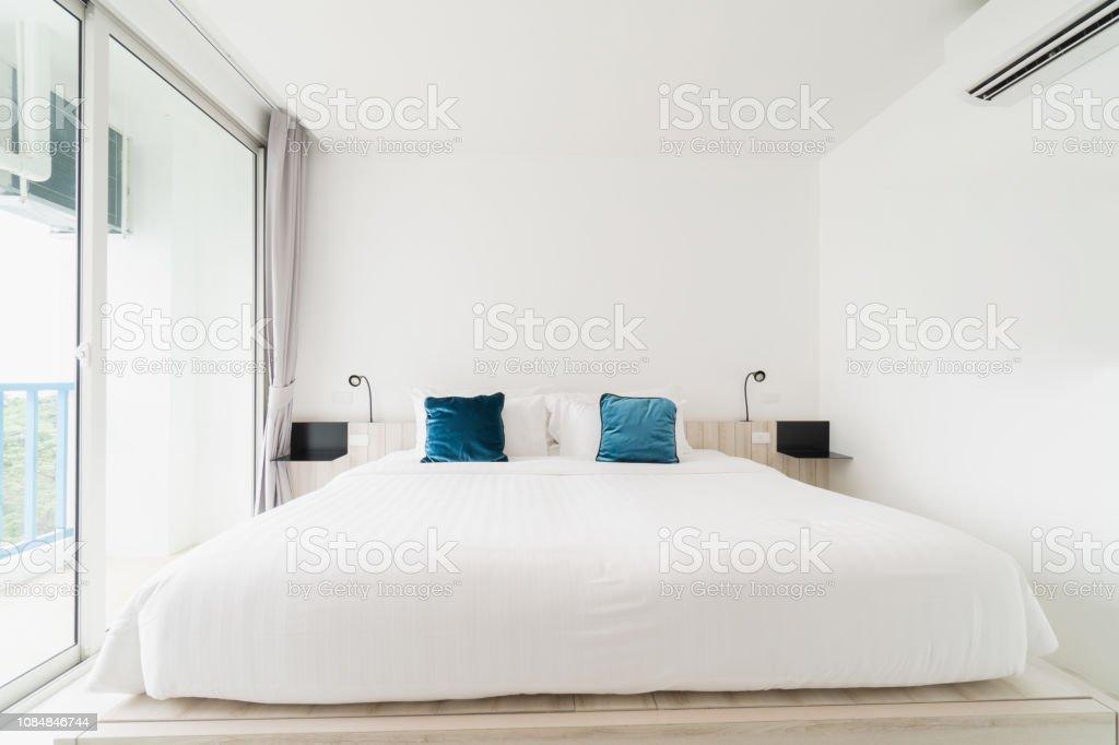 photo libre de droit de une chambre blanche avec un lit en bois linge de lit et un oreiller avec manteau blanc bon pour se detendre la chambre blanche rend la salle