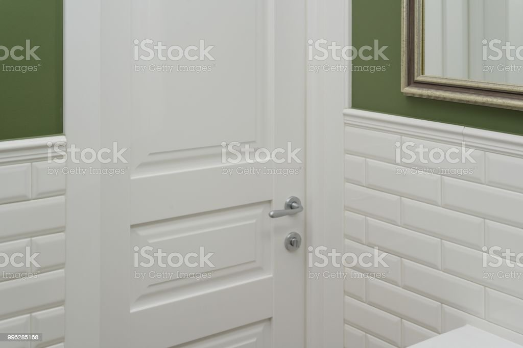 White Door In The Bathroom Toilet Room Background Green Painted Wall Covered With Decorative Ceramic Tiles With White Glossy Bricks Interior Details Closeup Stock Photo Download Image Now Istock