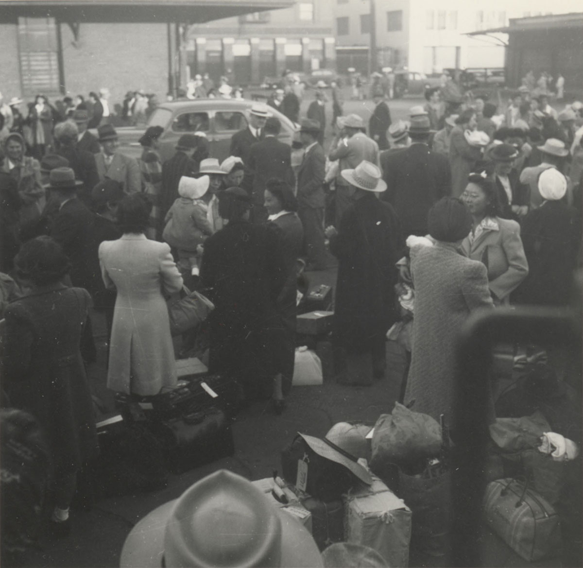 Japanese Americans wait at the old Santa Fe Station, Los Angeles, California. They are bound for Parker, Arizona (Poston concentration camp), May 29, 1942. Gift of Susan K. Mochizuki and Ann K. Uyeda.