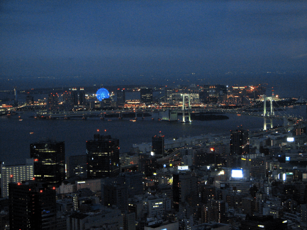 Odaiba at night. The Rainbow Bridge can be seen from afar. Source.