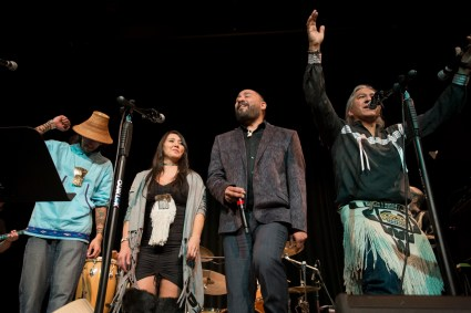 Four people dance and sing into microphones. Vocalists Nahaan, Sondra Segundo, Stephen Blanchett and Gene Tagaban sing with Khu.éex' at Centennial Hall on Monday, January 28, 2019. The Seattle-based band played the 16th Annual World Music Celebration in Anchorage before their Juneau concert. (Photo by Annie Bartholomew/KTOO)