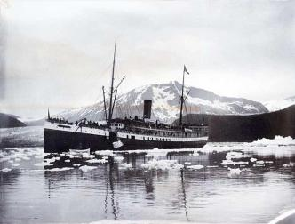 Steamer Queen taking on ice in Takou Inlet sometime between 1896 and 1913. Note the people standing on the deck and the net hauling up a piece of ice with the glacier in background. (P95-040 Alaska State Library - WLR Photo Collection)