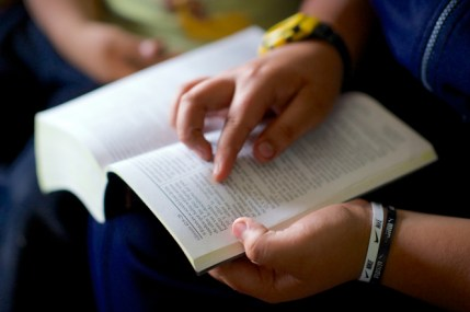 Two young boys sit together while one of them holds a paperback Bible in his hands and reads from the book of Genesis.