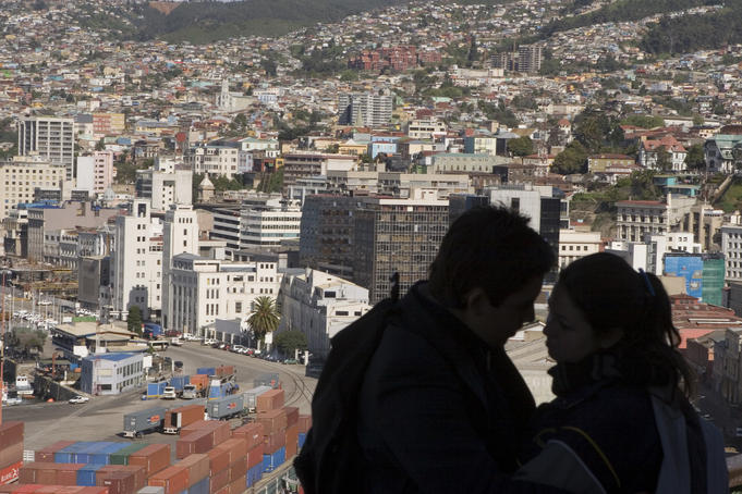 Young couple at summit of Ascensor Artilleria, with city buildings beyond.