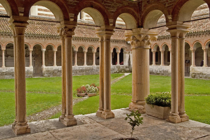 Cloisters attached to San Zeno Maggiore church with both rounded Romanesque and Gothic pointed arches.