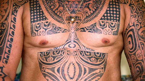 Man illustrated with Polynesian tattoos.