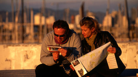 Couple consulting 'Lonely Planet' Barcelona guide.