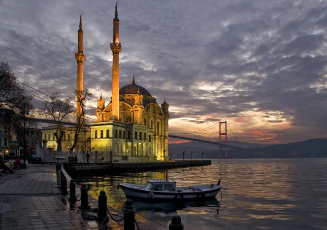Ortakoy Mosque looking towards the Bosphorus Bridge, under a cloudy sky.