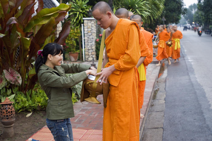 People giving alms (sticky rice) to monks during early morning procession on Thanon Sisavangvong street.