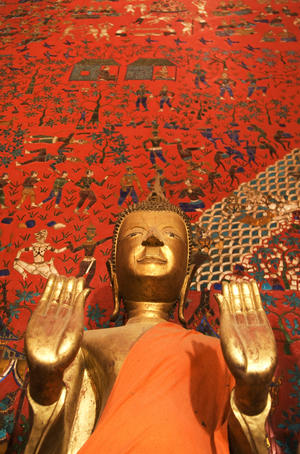 Buddha statue at Wat Xieng Thong, standing in front of mural.