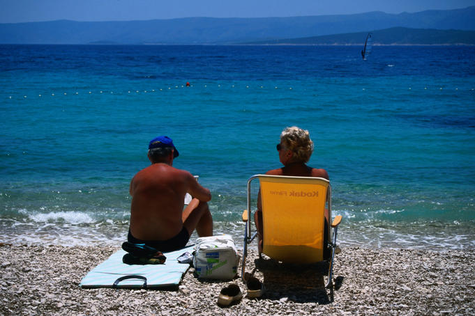 A middle-aged couple soaking up the sun on a pebble beach.