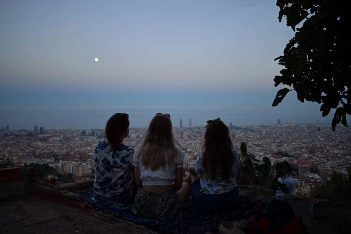 tre tjejer sittandes framför utsikt över barcelona