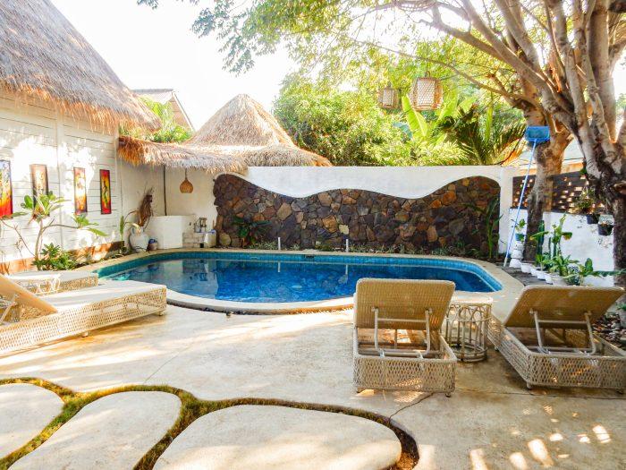 pool och solstolar på gili breeze tropical bungalows. på trawangan.