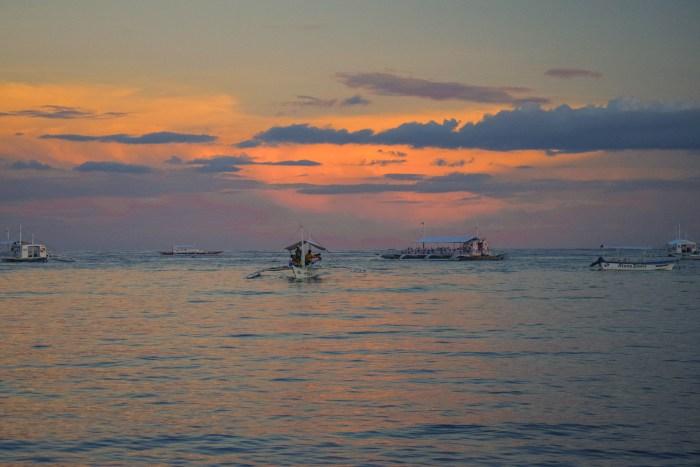 båtar ute på havet med rosa himmel.