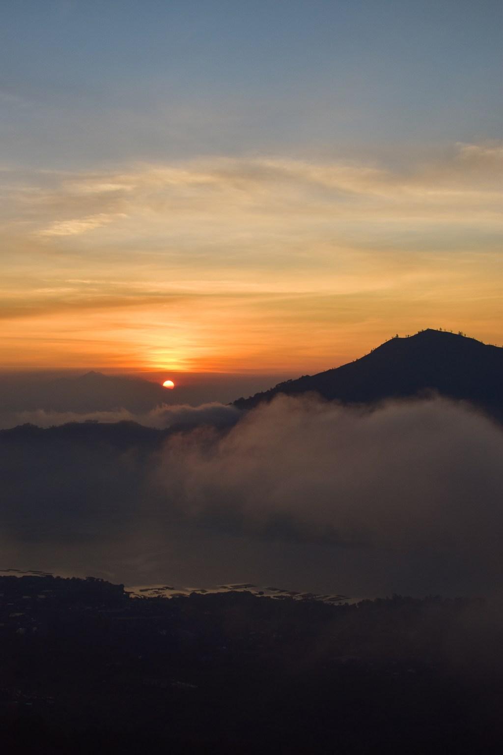 solen går upp vid horisonten vid mount agung.