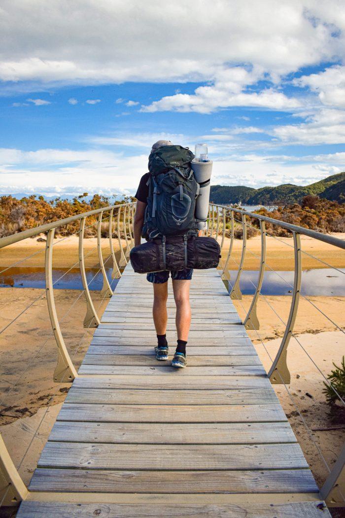 david vandrar över bro i abel tasman nationalpark.