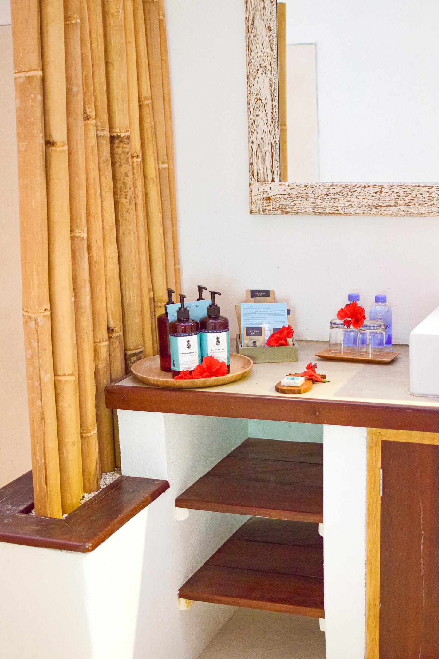 shampo, balsam och vattenflaskor vid handfatet.