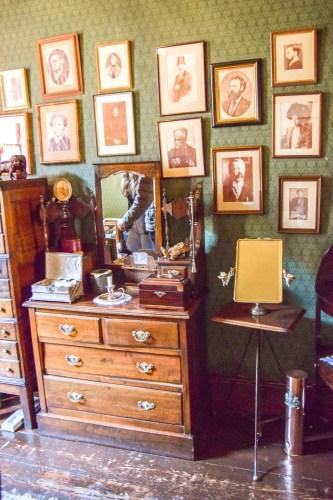en byrå vid en vägg med många fotografier.