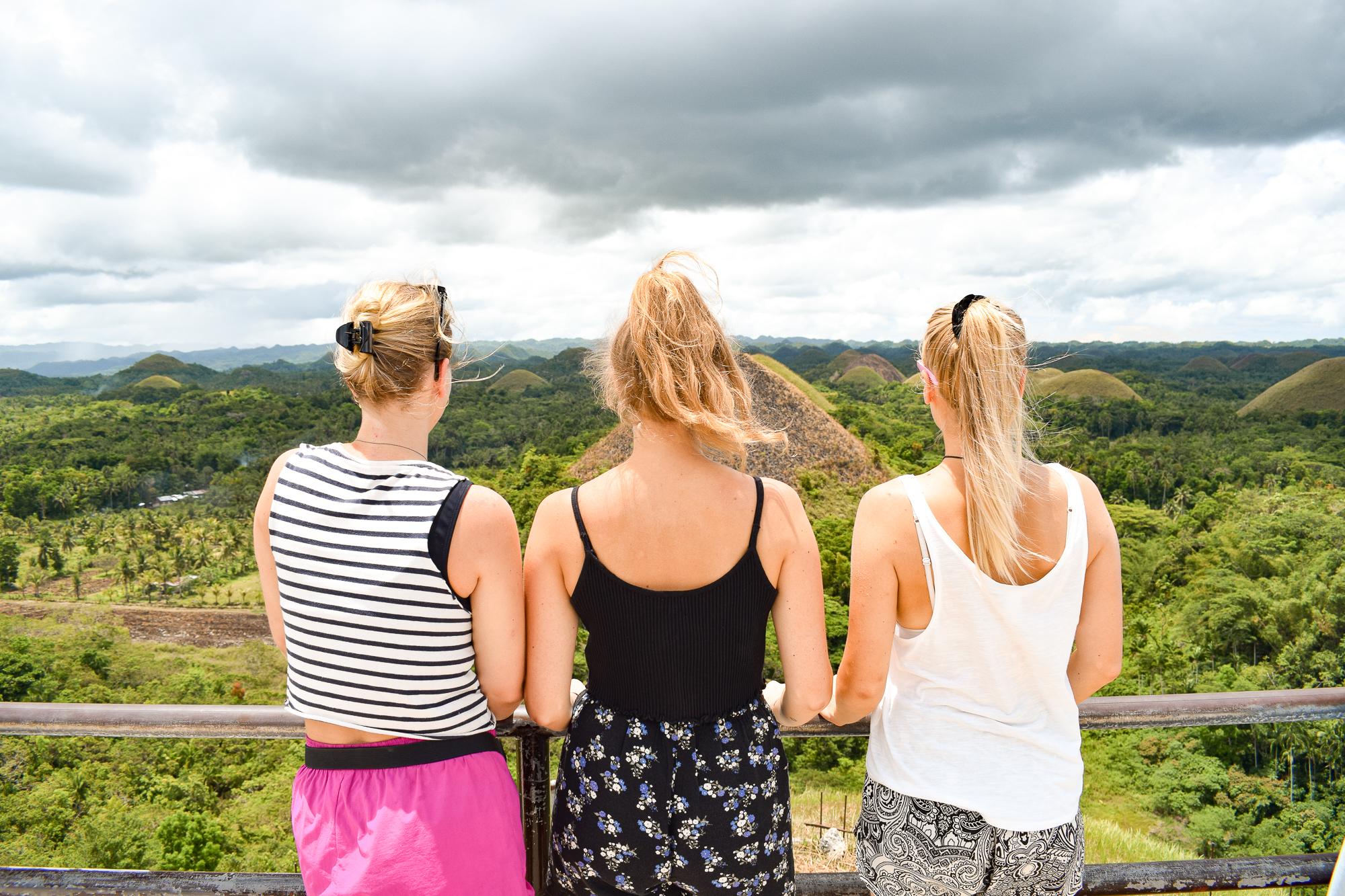 tre tjejer tittar ut över Chocolate hills.