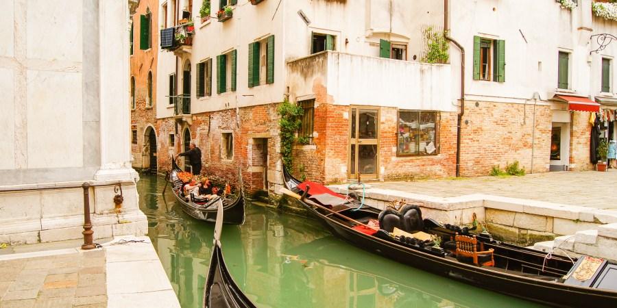 gondoler ligger i kanalen, en gondol åker förbi dem.