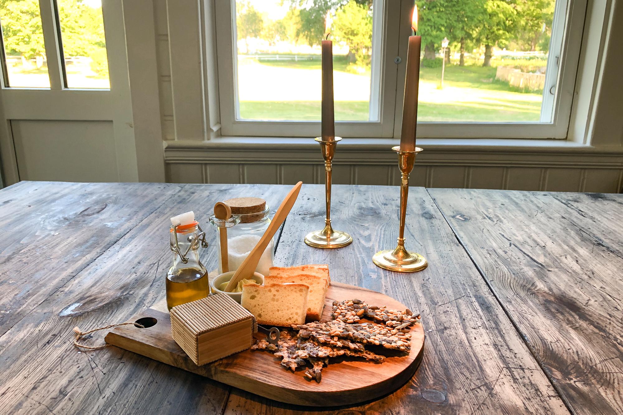 Träbricka med smör och smör med ljusstakar i bakgrunden.