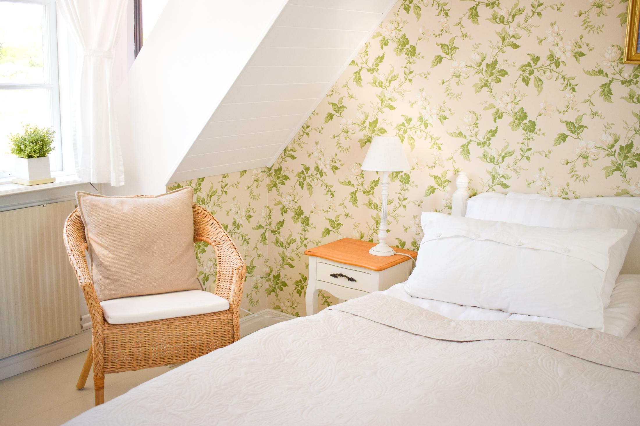 rottingstol, säng och sängbord.
