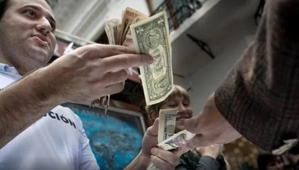 """Los llamados """"arbolitos"""" cambian dólares en la calle."""